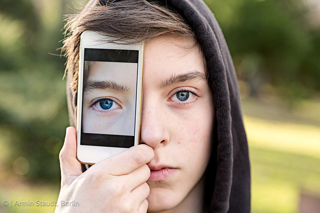 virtual realty, teenage boy holding a smart phone in front of his face
