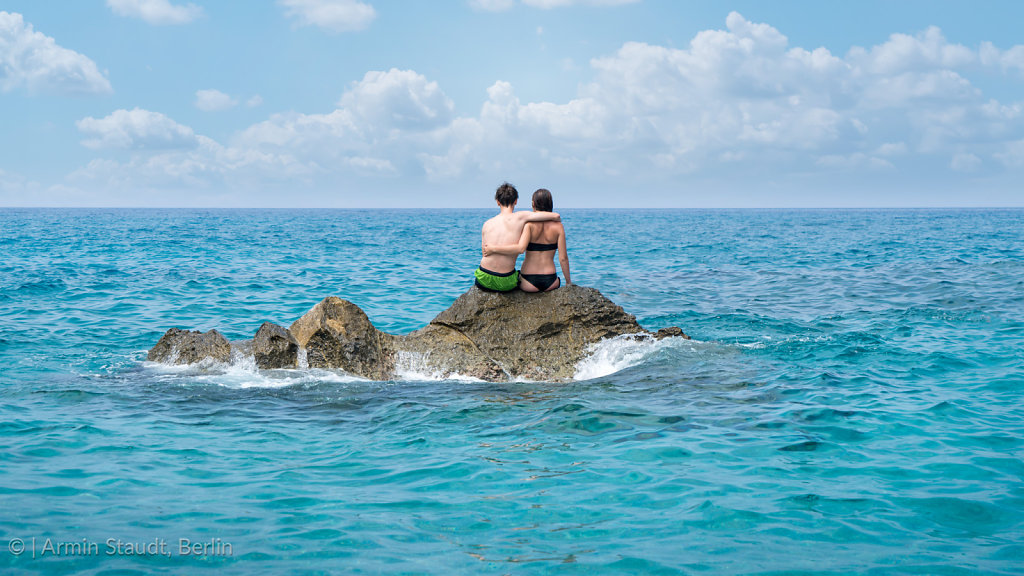 Young couple sitting on a cliff in the middle of the sea