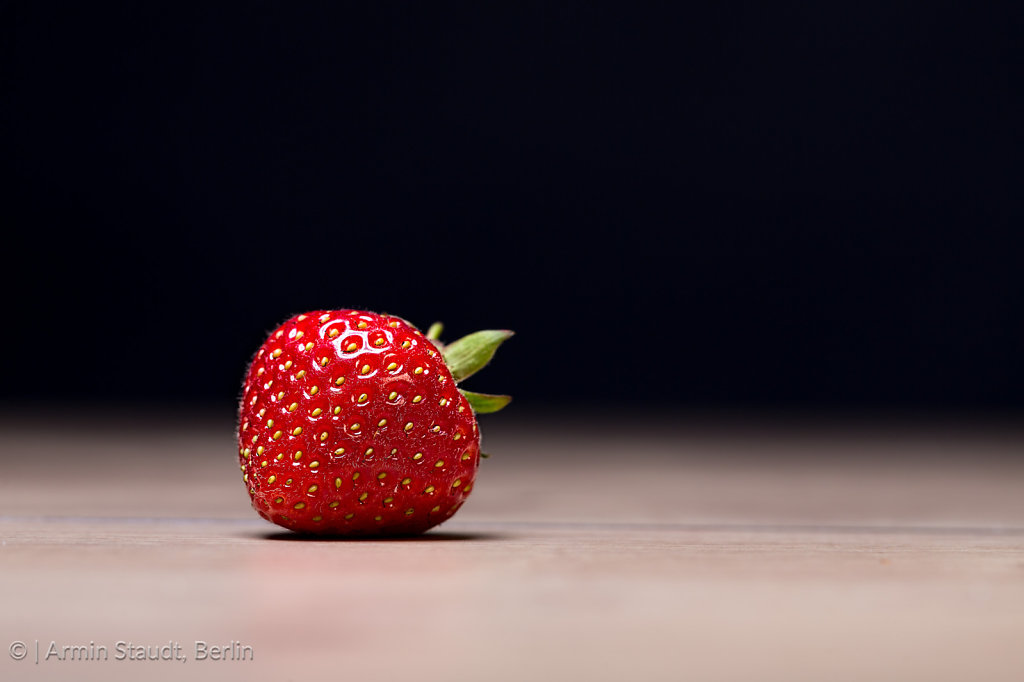 single strawberry on a table with black background