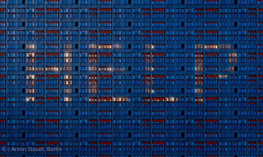 the word Help written with enlighten windows of a dark skyscraper