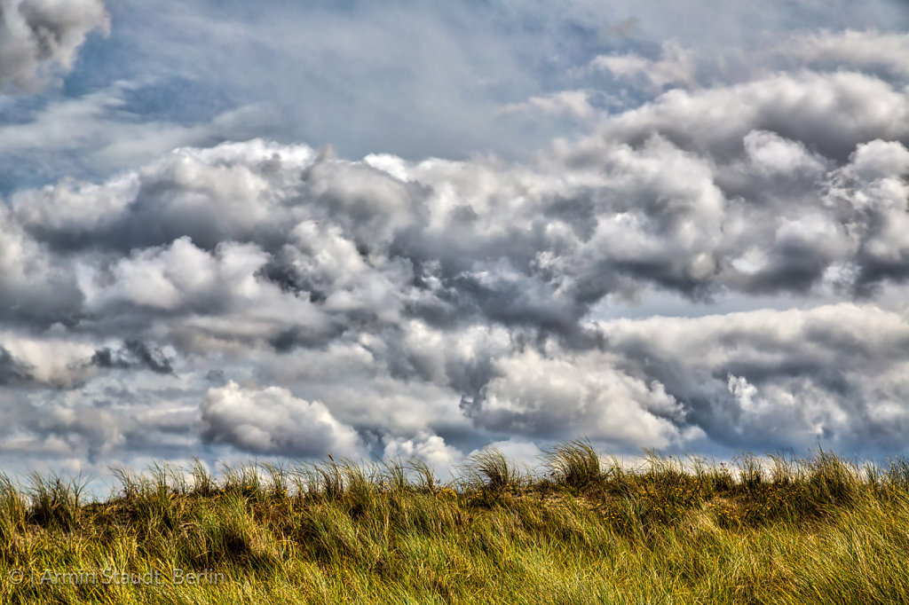 HDR stormy cloudscape and grass dune