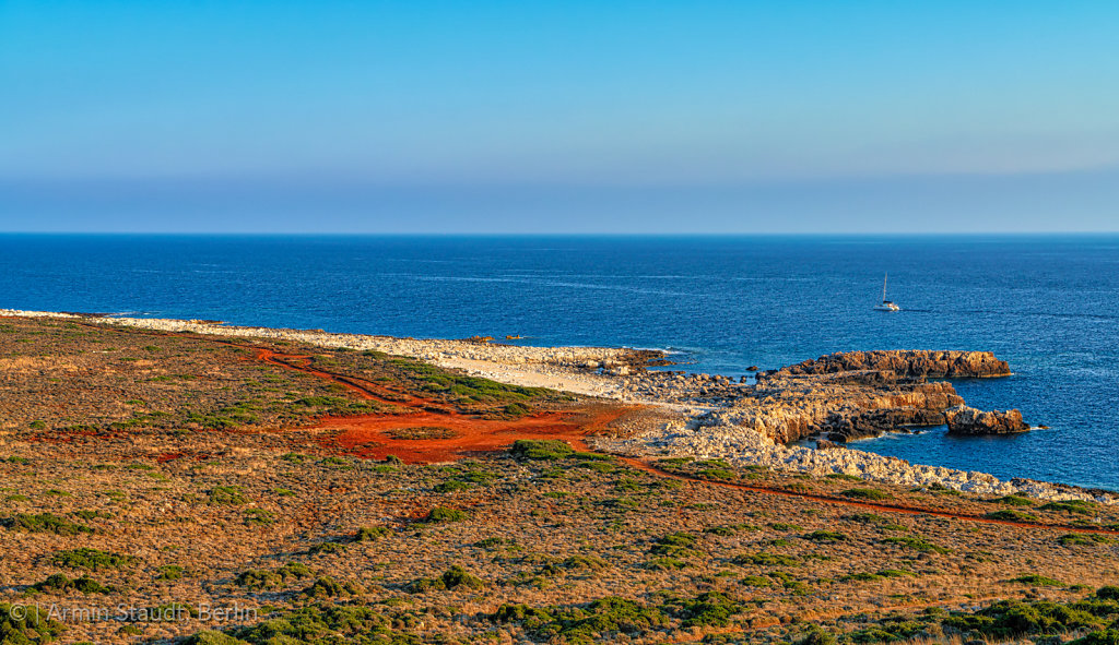 mediterranean landscape with red sand, ocean an clear blue sky
