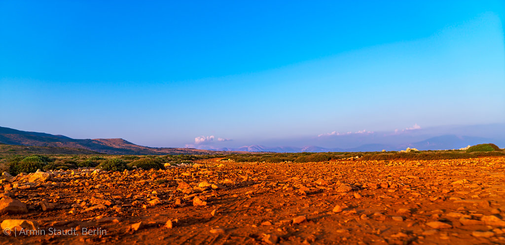 landscape in the evening with red stones and mountain range