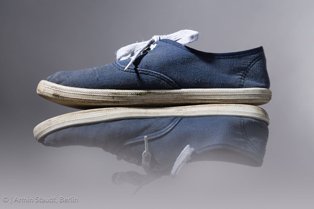 old, blue sneakers with gray background