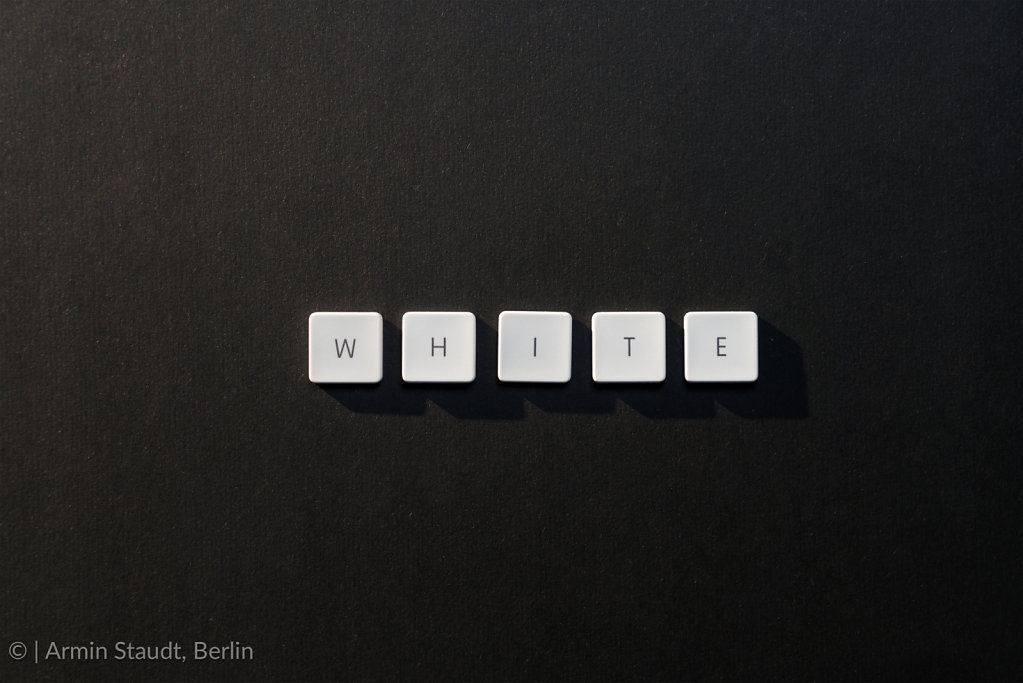 description of the word White with keyboard letters on black bac